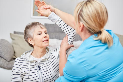 therapist helping a woman with shoulder mobility