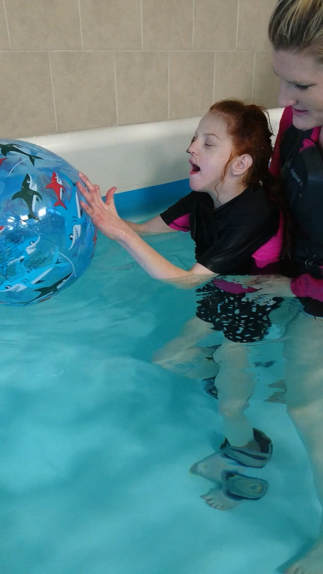 child playing with ball in pool